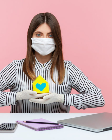 Renting during coronavirus quarantine. Woman real estate agency sitting at workplace, wearing hygienic mask and protective gloves, holding paper house, offering help in mortgage issues, home insurance