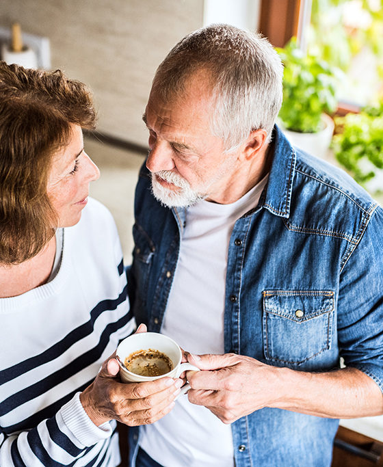 Senior couple talking in the kitchen. An old man and woman inside the house, holding a cup of coffee.